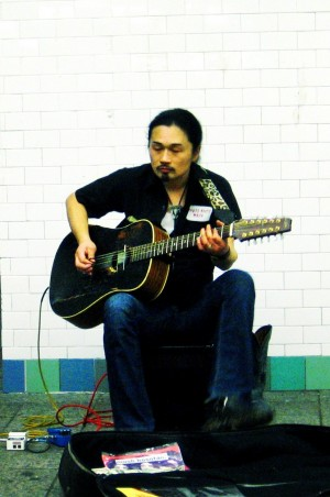 A New York City musician playing guitar in the Times Square subway station in NY. Photo Credit: Mo Riza. Photo Courtesy of: Wikimedia Commons.