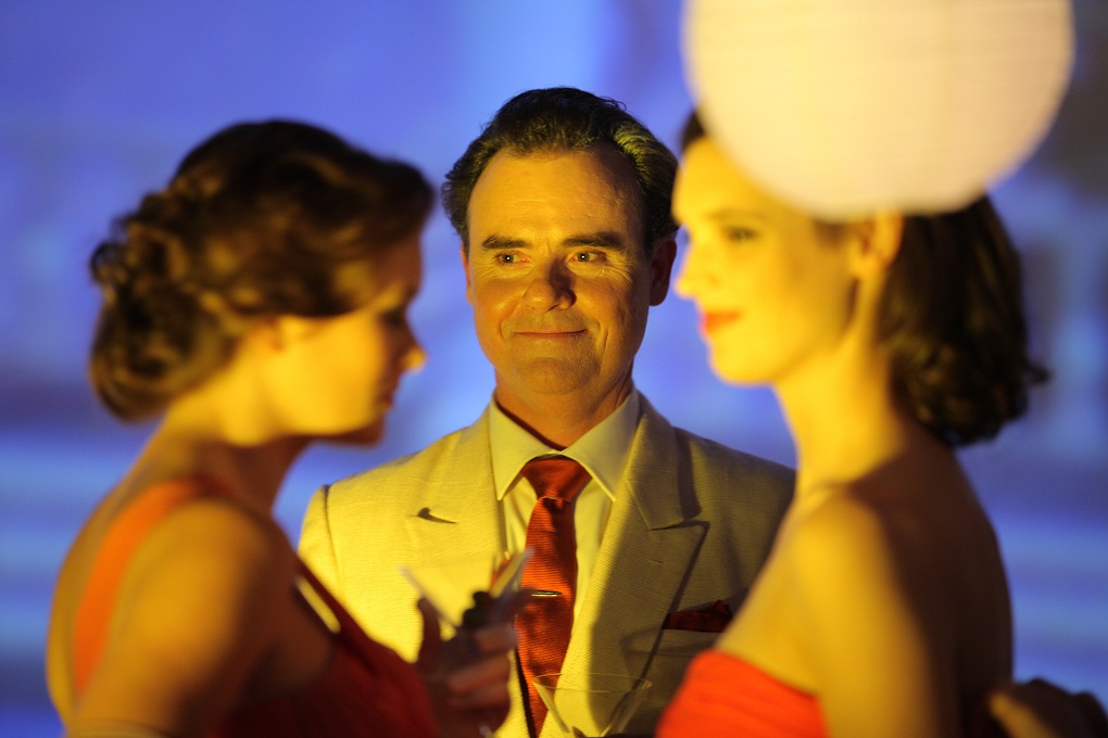 Orry-Kelly played by Darren Gilshenan with cocktail party guests. Photo: Hollywood Classics.